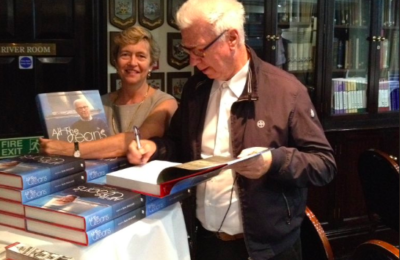 "Ron Holland signs copy of his book ""All The Oceans"" for library of Little Ship Club London, Vivien Godfrey of Stanfords Books and Charts is lending a helping hand"