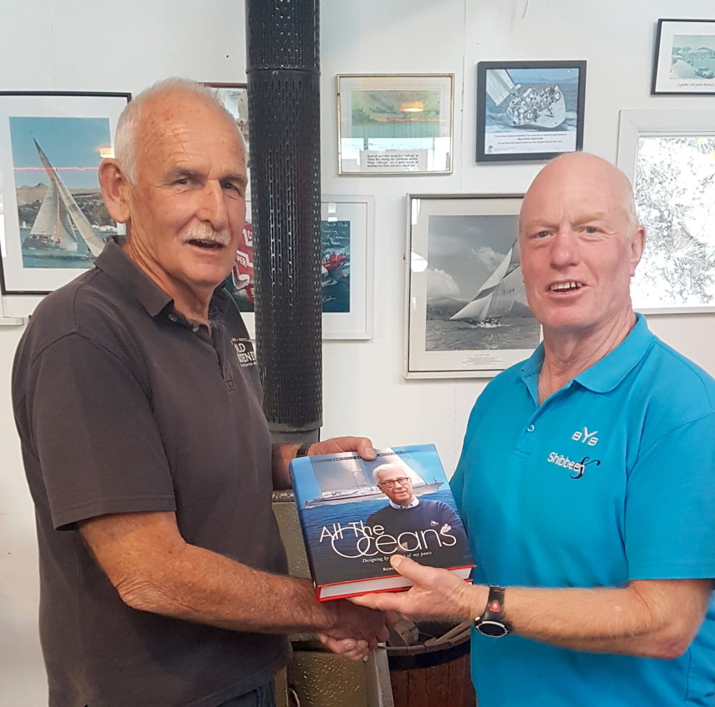 Willie Newman Little Ship Club Canterbury presents Commodore Colin Lock of Naval Point Club Lyttelton a copy of Ron Holland's memoir All The Oceans for the club library