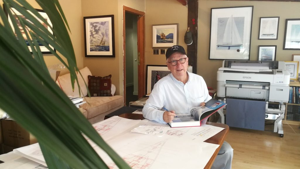 Ron Holland at the Ron Holland Design office, signing a copy of his memoir All The Oceans