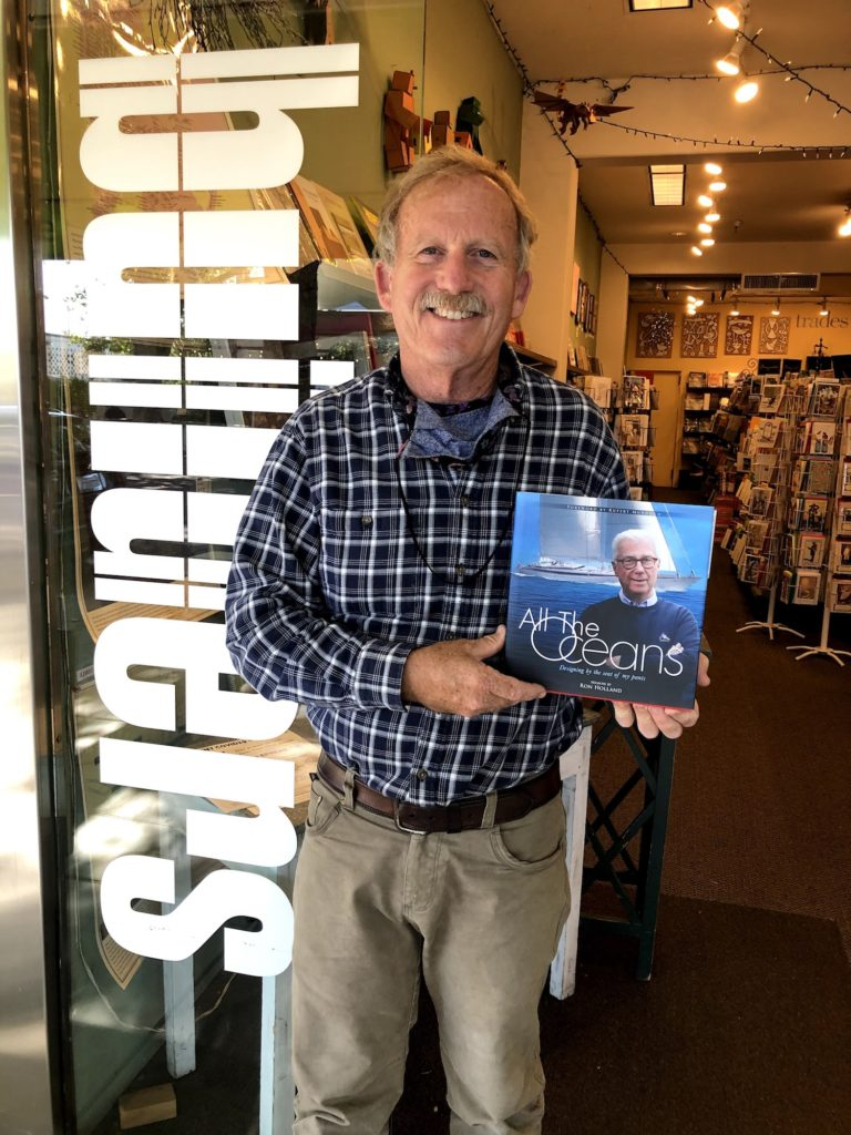 George Kiskaddon with a copy of Ron Holland's All The Oceans at his Builders Booksource shop in Berkley CA