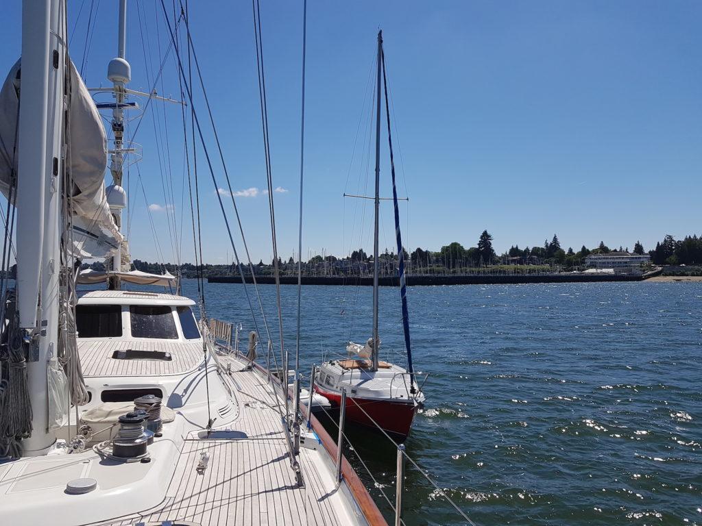 Kia Aura a red hull 25 foot Coronado along side superyacht Avalon
