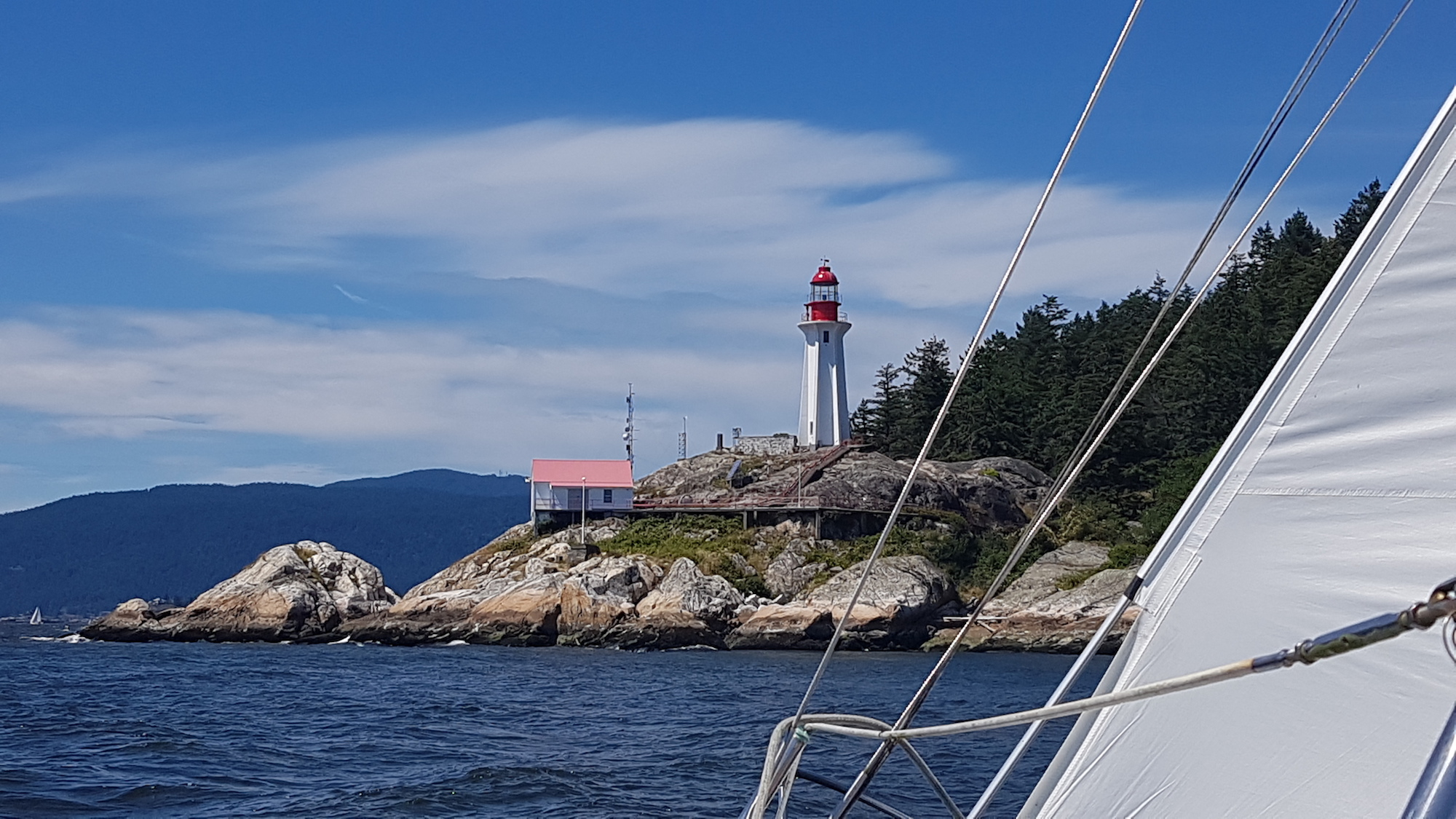 Historic Point Atkinson Lighthouse with a peek of the sheet on Kia Aura sailing past on a summer day