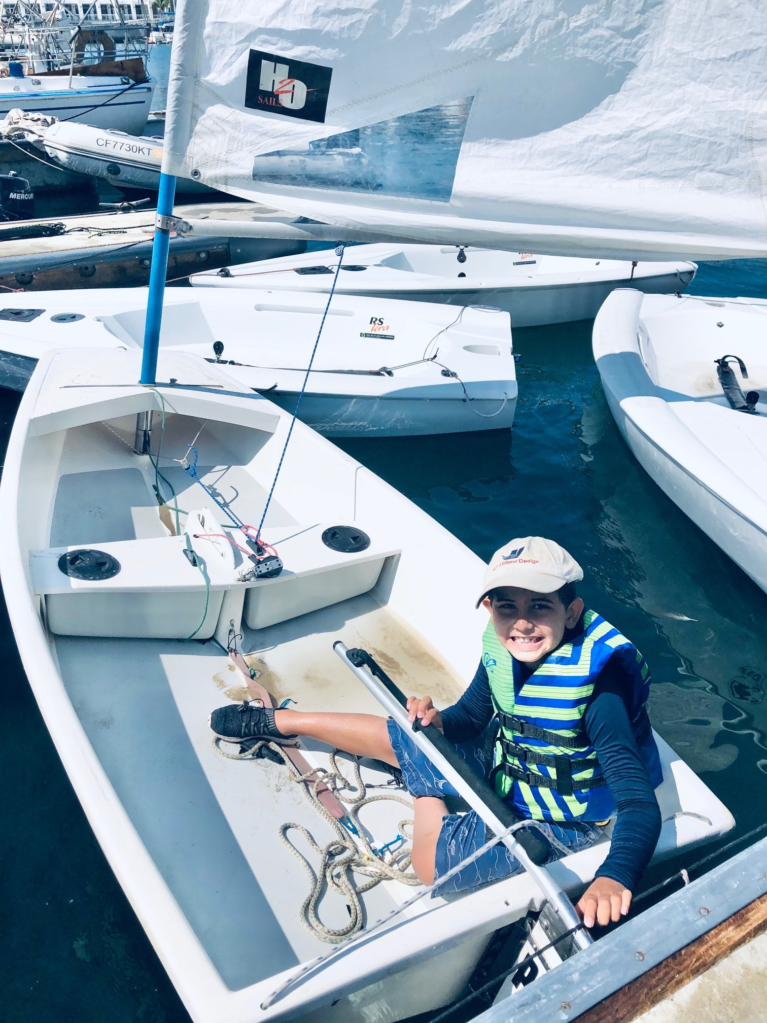 Wearing a Ron Holland Design hat young sailor ready to sail as he sits in his boat among a flotilla