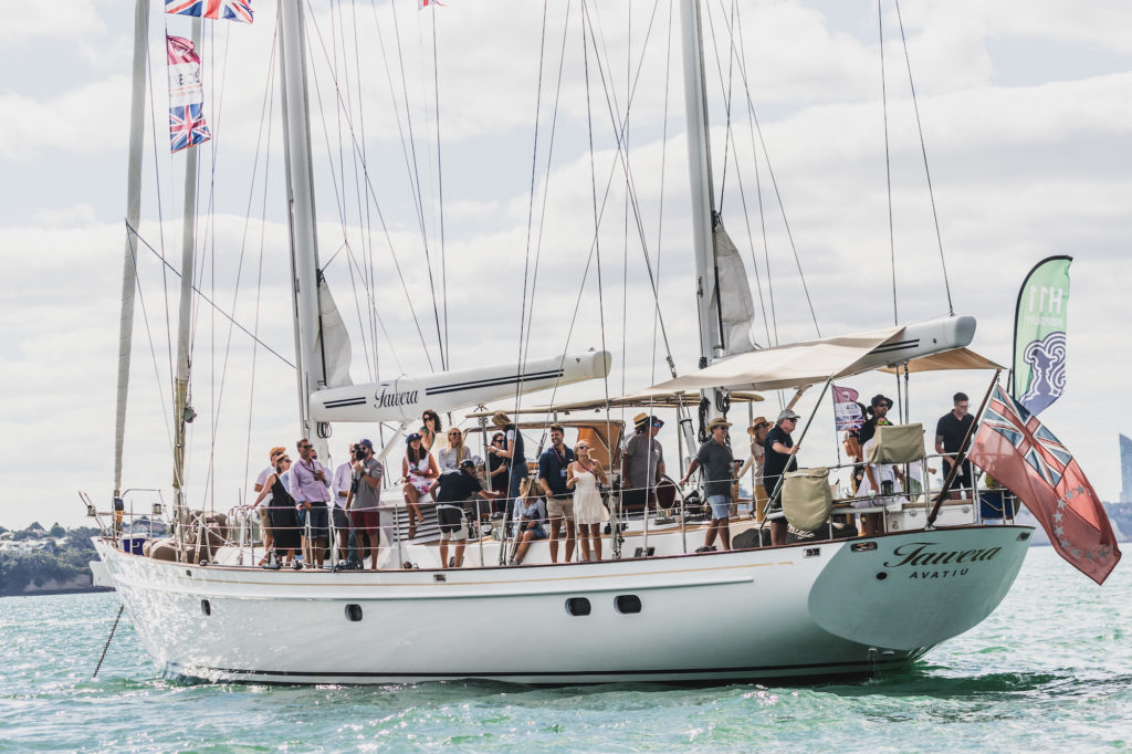 Sailing yacht Tawera at the Prada Cup January 2021 seen on the waters of Waitemata Harbour, Auckland, New Zealand with celebration aboard the deck of this racing yacht